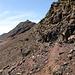 Steile Felsen versperren die direkte Gratroute hoch zur [point124115 Terraza Grande]. Daher geht's links (östlich) direkt unter den Felsen entlang weiter bis das Gelände einfacher wird, und man weglos ein paar Dutzend Höhenmeter nach rechts zum Grat hochsteigen kann (T3, Pfadspuren, etwas sandig-rutschig, aber nicht ausgesetzt).<br />