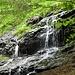 Kleiner Wasserfall neben dem Steig, das Wasser fließt über den Steig ab.