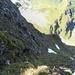 Jäher Tiefblick aus der Scharte am Gipfelgrat des Gamsberg auf die Austiegsroute durch die Nordflanke. Die Route folgt der seichten Schrofenrinne über das obere Schneefleckchen hinweg