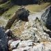 Gamschopf Westgrat Schlüsselstelle. Am Beginn der roten Linie bei den überhängenden Felsen ist es etwas knifflig sowie leicht brüchig. Im Vordergrund ist es auch Kletterei im II. Grad.