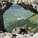 Rückblick durch Felsfenster. Unten Mauren (FL). Schräg rechts auf der Waldlichtung direkt neben der grasigen Felsspitze: Gafadurahütte.
