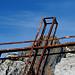 Ein Gipfelkreuz, das schon bessere Zeiten erlebt hat, vor dem Gipfel des Torrione