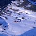 Tiefblick auf verschneite Alpen und Strukturen im Schnee