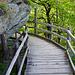 Holzbrücke um eine Felsnase herum