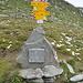 Der Wegweiser auf dem Tomülpass (2412 m). Davor der Gedenkstein für die polnischen Internierten, die den Passweg vom Safiental her auf den Pass gebaut haben.