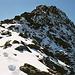 Auf dem verschneiten Grat taucht das Gipfelkreuz des Bristen auf.