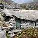 <b>Sprügh. <br />Gli alpigiani sfruttavano la sporgenza o la rientranza di una roccia oppure lo spazio coperto risultante da un enorme macigno crollato su altri blocchi, chiudendone i vuoti con dei muretti a secco e una porta.</b>