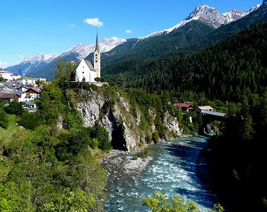 Blick von der Gurlainabrücke auf den Kirch-Hügel und die gedeckte Holzbrücke von Scuol