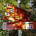 Gipfel Kékestető - Wegweiser. Wie man sieht, gibt es eine ganze Reihe markierter Wanderwege. Unser blau markierter Weg über die Südliche Skibahn (Délí Sípálya) ist mit einer Länge von 4 km ausgewiesen.
