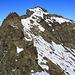 Aussicht vom Bocktenhorn Sügipfel P.3019m zum 3044m hohen Hauptgipfel. Um dorthin zu gelangen musste ich zuerst auf dem Grat etwas ausgesetzt abklettern (Schlüsselstelle; T5+ / Fels II-), danach konnte ich ostseitig (rechts) unter den Gratfelsen traversieren um danach über Geröll und Schnee zum Hauptgipfel aufzusteigen.