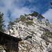 Hinter der Hütte ist der Einstieg in den Südwestgrat: Der markierte Pfad führt links um den Gipfelkopf herum und von hinten über eine Drahtseilpassage nach oben.