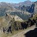 Abstieg über Büion zur Senda del Bo, zu der die charakteristische Grasrampe in der Bildmitte führt. Im Mittelgrund die Türme des Piz di Strega WNW-Grat, davor der Pizzo Bòrsgen, dahinter das Rheinwaldhorn