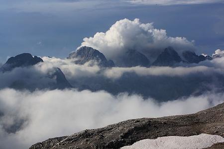 Aussicht vom Triglavski dom na Kredarici (2515m) nach Norden wo links der grossen Quellwolken der Stenar (2501m) und die Dolkova špica (2591m) stehen. Rechts schaut der Spodnji Rokav (2500m), ein Vorgipfel des Visoki Rokav (2646m) aus der Wolke.