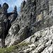 Nach der Querung des Bandes - gleich die vertikale Schlüsselstelle (Bildmitte und links davon).<br />Der Klettersteig zieht ab dem linken Felsvorsprung (Kletterer) nur noch ca. 200mH senkrecht nach oben.