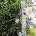 """In der hellen Alu-Dose neben dem Kreuz befindet sich das komplett aufgeweichte """"Gipfel?""""-buch."""
