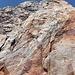 Unter dem Gipfelkopf. Das Fixseil führt bis zu einem Band, das den Aufstieg über die obersten Gratfelsen ermöglicht. Alternativ kann man auch der Verschneidung weiter folgen (steiler, dafür objektiv etwas weniger exponiert).