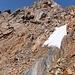 Unter dem Gipfelkopf steigt man entlang und an brüchigen Felsen etwas in die Westflanke ab.