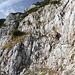 """Im Aufstieg zum Maglić / Маглић (Route durch die Ostflanke) - Gut getarnt wird eine leichte, drahtgesicherte Kletterstelle überwunden. Der riesige Markierungspunkt links ist fast besser als """"die erste Hälfte unserer Wandergruppe"""" zu erkennen."""