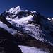 Die stark vereiste Norwand des Piz Roseg (3937m). Der Hauptgipfel ist der Felsaufbau links hinter der Schneekuppe, dem scheinbar höchsten Punkt. Durch den Bildvordergrund ziehen die beiden Gletscherarme des Tschierva-Gletschers.
