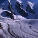 Die drei Gipfel des Piz Palü über den drei Felspfeilern: links der Ostgipfel (3882m) über dem Kuffner-Pfeiler, in der Mitte der Hauptgipfel über dem Bumiller-Pfeiler und rechts der Felsgipfel des Piz Spinas (3823m) über dem Westpeiler. Durch den Bildvordergund fließt der breite Strom des Persgletschers. Aufgenommen von der Diavolezza-Hütte.