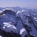Blick vom Gipfel des Piz Bernina nach Westen, auf die Nordwand des Piz Roseg (3937m) mit ihren gewaltigen Hängegletschern. Im Hintergrund ist die Silhouette der Granitkette der Bergeller Alpen zu sehen.
