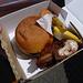 Der Klassiker in Tansania; Lunchpaket, mit Hamburger, Muffin, zwei Bananen und einem Stück Huhn.
