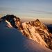 Zumsteinspitze (4563m), Dufourspitze (4634m) und Nordend (4609m) werden von der aufgehenden Sonne angestrahlt. Fotografiert von der Punta Gnifetti.